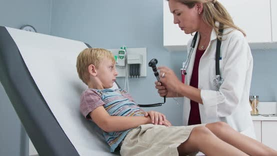 Female pediatrician checking ears of young boy in clinic exam room
