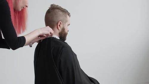 Young Red Haired Female Hairdresser Is Cutting Hair of Bearded Man Client