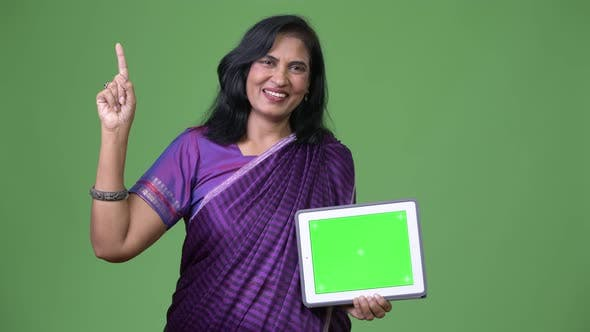Thumbnail for Mature Happy Beautiful Indian Woman Showing Digital Tablet and Pointing Finger Up