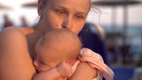Mum with baby on the beach at sunset
