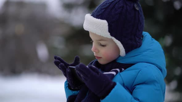 Thumbnail for Kleiner Junge im Winter tragen mit Telefon an kalten verschneiten Tag