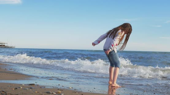 Little Girl Playing on the Beach in Summer
