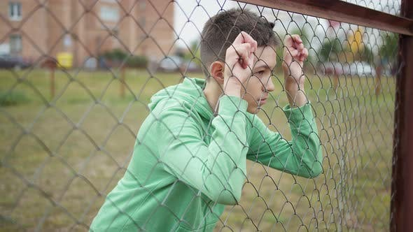 Refugee Serious Boy Stands Alone Head Bowed Near the Fence Regrets Actions
