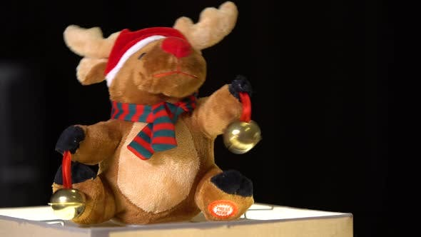 Thumbnail for A Dancing Plush Christmas Reindeer Toy with Jingle Bells - Closeup - Black Background