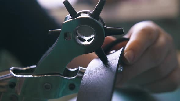 Tailor Makes Holes in Belt with Special Punch Pliers Closeup