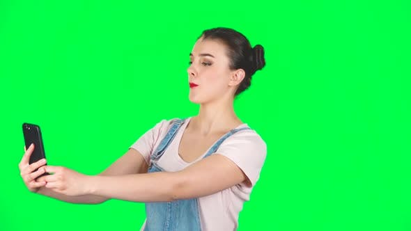Thumbnail for Girl Makes Selfie on Mobile Phone Then Looking Photos on Green Screen, Slow Motion