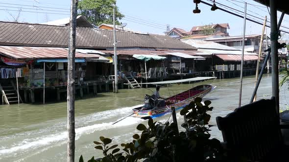 Thumbnail for The Tha Kha Floating Market with a speeding boat passing by
