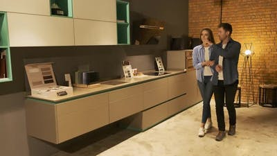 Couple Browsing Samples of Furniture in Modern Kitchen Showroom. Home Remodeling, Renovation and