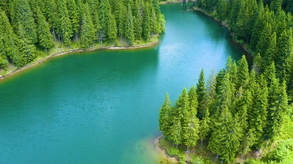 Thumbnail for Aerial view over beautiful turquoise mountain lake and green forest. Summer in the mountains.
