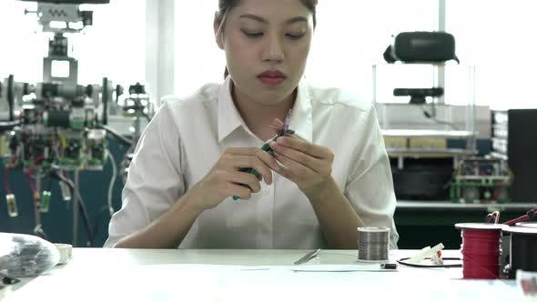 Young woman learning hardware in classroom