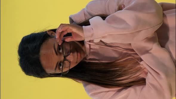 Multiethnic Young Woman Looking Over Her Glasses on Yellow Background.