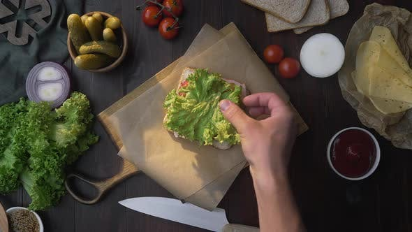 Thumbnail for Flat Lay of Making the Sandwich with Sliced Bacon and Salad, Chef Adds Salad To the Sandwich on the