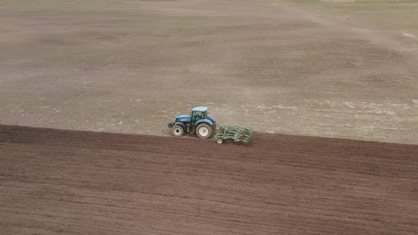 Tractor Plows the Field. Preparation of Soil For Sowing