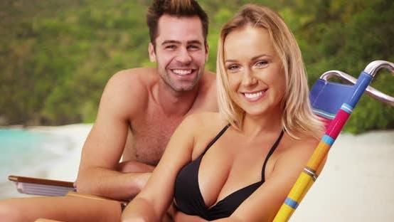 Thumbnail for Millennial couple sitting together at the beach being silly smiling at camera