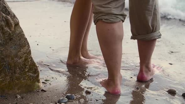 Cover Image for A Couple Is Walking Along the Beach on a Clear Sunny Day. They Hold Hands and Kiss. The Feet of Men