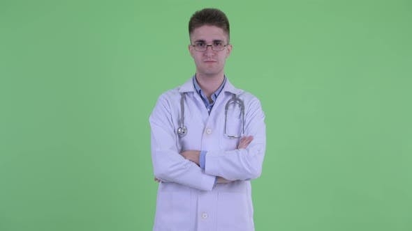 Thumbnail for Happy Young Man Doctor Smiling with Arms Crossed