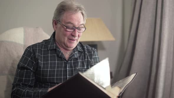 Portrait of Positive Caucasian Retiree Turning Pages of Photo Album and Thinking, Camera Approaching