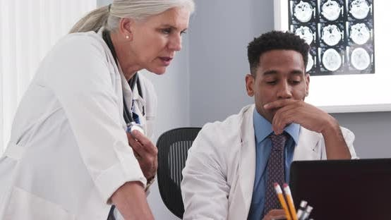 Thumbnail for Young black doctor consulting with elderly senior colleague on patients file