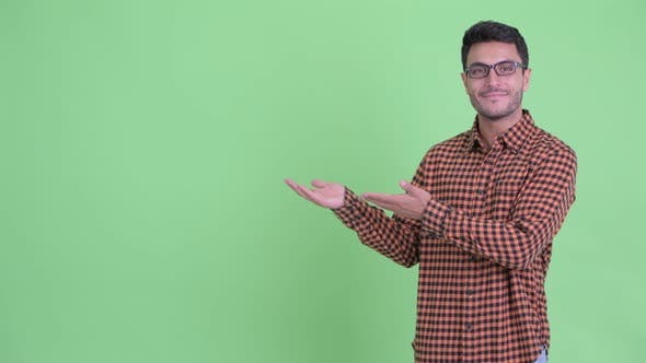 Thumbnail for Happy Young Hispanic Hipster Man Showing Something and Giving Thumbs Up