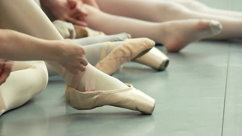 Group of Young Ballerinas Taking Off Pointe Shoes