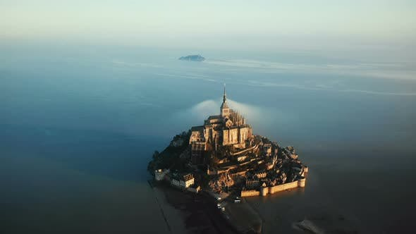 Cinematic Aerial Shot of Ethereal Sunrise Mont Saint Michel Island Castle Surrounded By High Tide