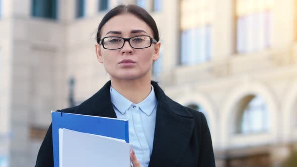 Portrait of Young Confident Business Woman Holds Folders with Documents in Her Hands. Attractive