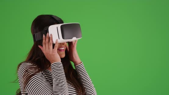 Thumbnail for Latina woman with virtual reality goggles on looking around on green screen