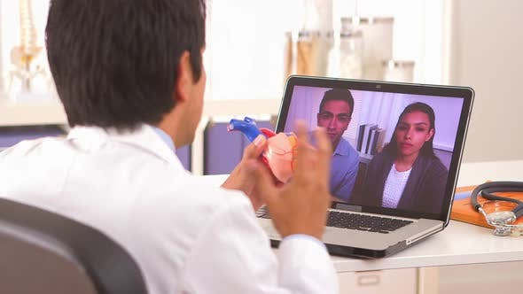 Cover Image for Hispanic doctor explaining heart procedure to couple