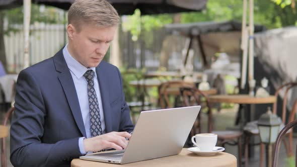 Thumbnail for Businessman working on Laptop while Sitting in Outdoor Cafe