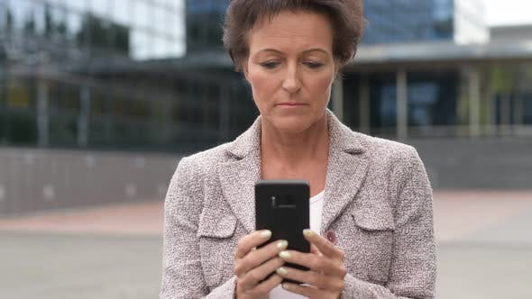 Cover Image for Happy Mature Businesswoman Using Phone In The City Outdoors