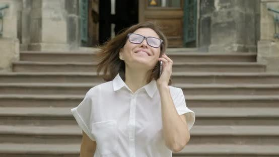 Thumbnail for Mature Smiling Positive Woman in Glasses Light Blouse Walking on the Stairs Talking on the Phone