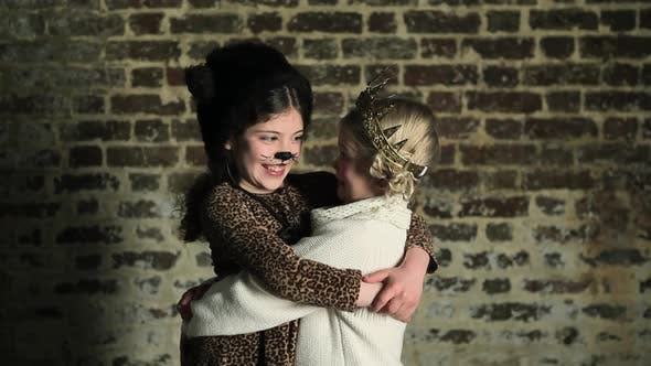 Thumbnail for Two young girls in dressing up clothes, hugging