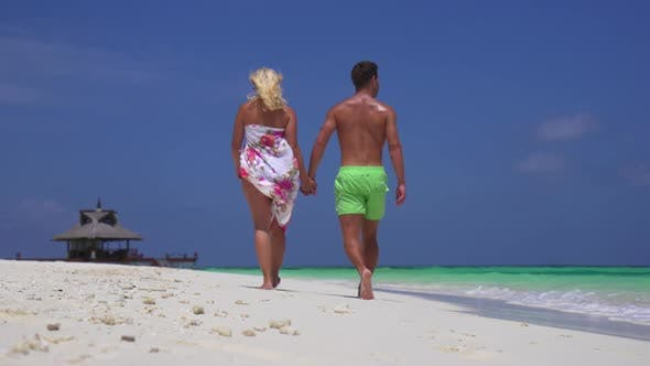 Thumbnail for A couple walks on the beach holding hands at a tropical island resort hotel.