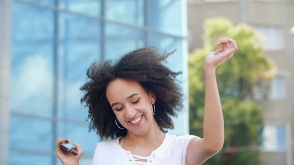 Thumbnail for Happy Laughing White-toothed African American Girl Model Jumps High and Rejoices with Smartphone in