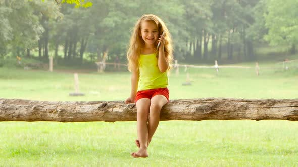 Thumbnail for Adorable Little Girl Talking on Smartphone Sitting in a Tree