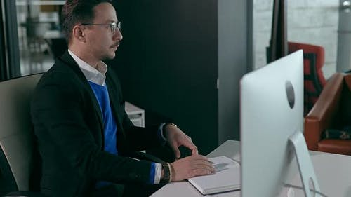 Businessman in Glasses Sits at Computer in Office and Writing It Into a Notebook
