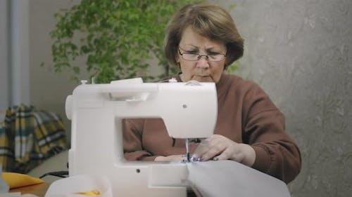 Senior Woman Sewing At Home