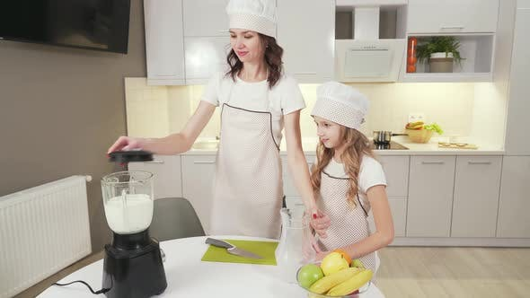 Thumbnail for Happy Mother and Pretty Daughter Doing Milkshake in Mixer