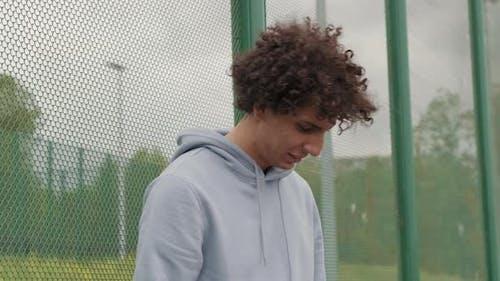 Porträt des jungen Mannes auf dem Basketballplatz im Freien