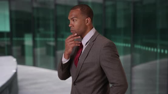 Thumbnail for African corporate employee thinking about something inside business building