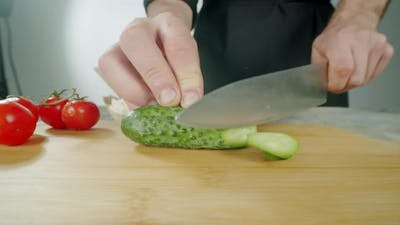 Knife Slicing the Cucumber Vegetables on Wooden Cutting Board