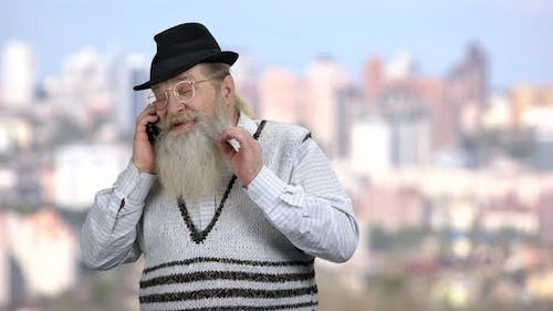 Bearded Man in Hat Talking on Cell Phone