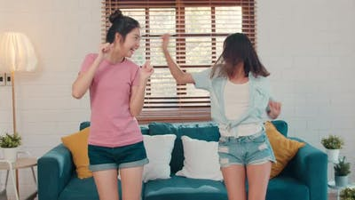 Asian Lesbian lgbtq women couple dancing at home.