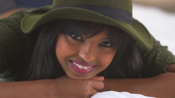 Thumbnail for African American girl wearing floppy hat on bed