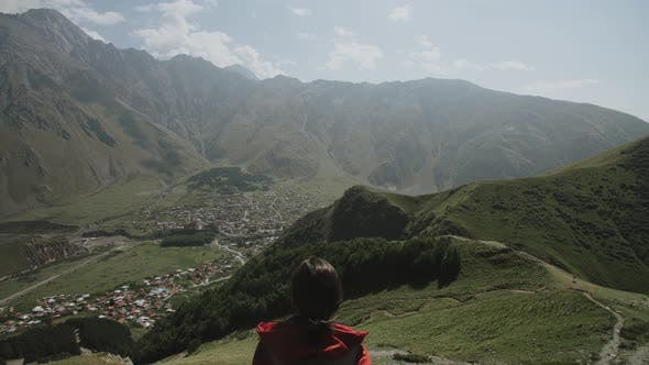 Thumbnail for Traveler Woman Sits on Cliff Mountain Gorge Looks at City Stepantsminda at Foot of Kazbek