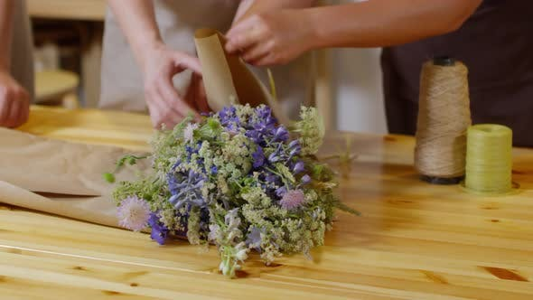 Thumbnail for Three Florists Wrapping Fresh Wildflower Bouquet