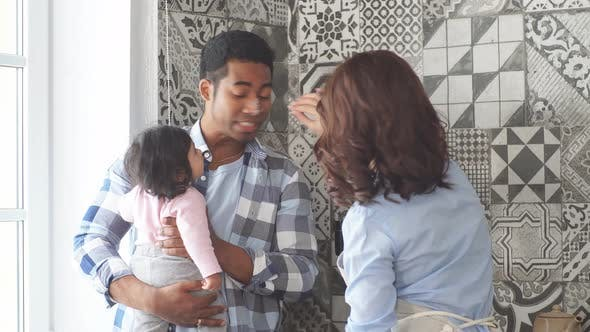 Thumbnail for Young Multi-ethnic Parents Smiling While Spending Time with Their Sweet Little Baby
