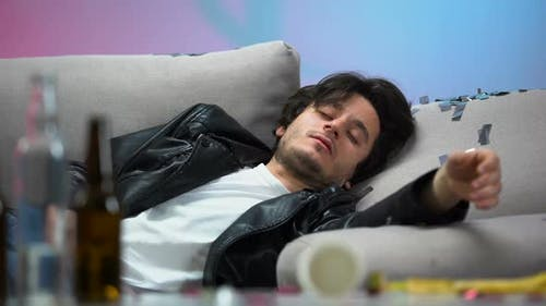 Drunk Young Man Sleeping on Couch After Night Long Party, Idle Life, Hangover