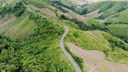 Aerial top view of sky road over top of mountain green jungle, Pua, Nan, Thailand.