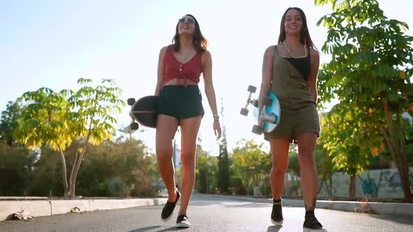 Thumbnail for Girlfriend Girls Go To the Park Holding Skateboards in Their Hands Talking and Laughing, Smiling at